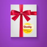 Box, red ribbon, bow and the badge Quality Royalty Free Stock Photos