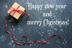 Box with red ribbon isolated on black background with falling snow and snowflakes. Congratulations on the new year and Christmas. New year and Christmas royalty free stock image