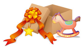 A box with a ribbon and a toy Stock Images