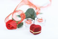 Box with ring, rose and two candles on white background Stock Photography