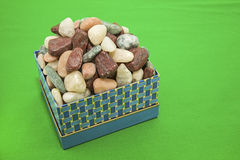 Box of rocks decorative green background Stock Photography