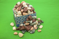 Box of rocks spilled green background Stock Photography