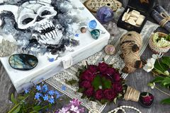 Box with scary demon face, magic mirror, voodoo doll and myctic objects on witch table. Occult, esoteric and divination still life. Halloween background with stock image