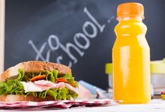 Box with school lunch near the black board. Healthy food for a child. Toast with salad and strawberries and blueberries and a. Bottle of juice. Food and books stock photo
