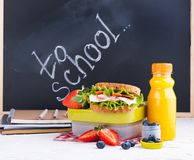 Box with school lunch near the black board. Healthy food for a child. Toast with salad and strawberries and blueberries and a. Bottle of juice. Food and books royalty free stock photography