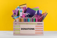 Box with school and office supplies with a sign on a bright yellow background. Donation concept royalty free stock photos