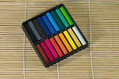 Box set of chalk. A box set of Colored chalk sticks on Bamboo mat Stock Photos