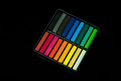 Box set of chalk. A box set of Colored chalk sticks isolated on black background Stock Images