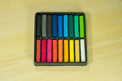 Box set of chalk. A box set of Colored chalk sticks on plank Royalty Free Stock Images