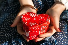 Box in shape of heart in female hands. Female hands keep box in shape of heart stock photos