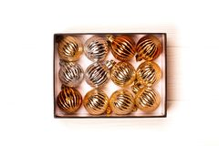 Box with silver and golden christmas balls on white wooden background. royalty free stock photo