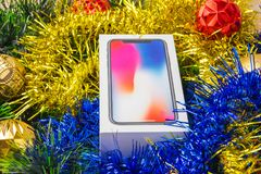A box with a smartphone in a Christmas tree tinsel. A sealed smartphone lies in Christmas toys Stock Images