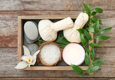 Box with spa cosmetics, accessories and orchid. On wooden background Royalty Free Stock Photo