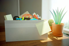Box with stationery items. Closeup of box full of stationery items, blank sticker a dn decorative plant on wooden desktop with daylight. 3D Rendering Stock Images