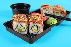 Box with sushi rolls on color background. Food delivery royalty free stock photos