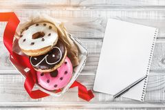 A box of sweet donuts, a red ribbon and a white sheet and a pen for a greeting message. Top view, advertising space stock image