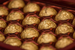 Box with sweets. Gift box with sweets in a golden wrapper Stock Photography