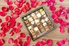 Box of tasty chocolates among rose petals - a romantic gift Royalty Free Stock Image