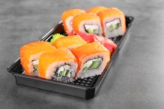 Box with tasty sushi rolls on grey table. Food delivery royalty free stock photo