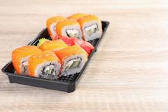Box with tasty sushi rolls on wooden table, space for text. Food delivery royalty free stock photo