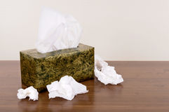 Tissue box with used crumpled tissues on a wood table, copy space Stock Image