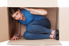 This box is too small. Shocked young woman looking at camera while sitting in a cardboard box Royalty Free Stock Image