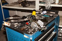 Box with tools and spare parts lying on it in disarray in the process of repairing the car in the workshop for vehicle royalty free stock image