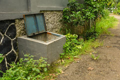 Box trash made with cement on side of house with bush and tree surrond in bogor indonesia Stock Photography