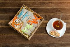 Box with treats. A bar of muesli and a mug of tea. Top view.  Royalty Free Stock Photography