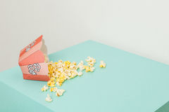 Box of two colors with popcorn. Popcorn spilled from a striped box isolated in a color background vector illustration