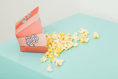 Box of two colors with popcorn. Popcorn spilled from a striped box isolated in a color background royalty free illustration