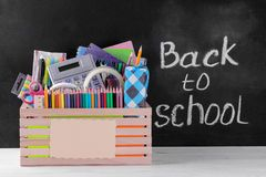 Box with various school and office supplies with a sign on the background of a school board royalty free stock photos
