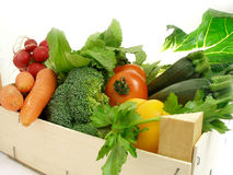 Box of vegetables. A cornucopia of vegetables coming from the market in a wooden box royalty free stock photo