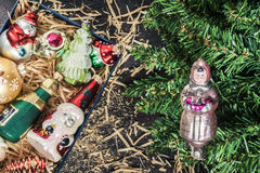 Box with vintage glass Christmas toys under the tree top view royalty free stock photography