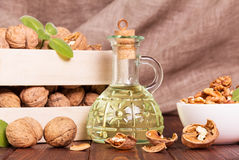 The box with walnuts and butter,   carafe of them on  abstract brown background Royalty Free Stock Photography