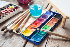 Box of watercolor paints, art brushes, glass of water and easel. With canvas or paper on old wooden table Stock Photos