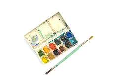 Box of watercolor paints and brush. Set of messy watercolors with small brush royalty free stock photos