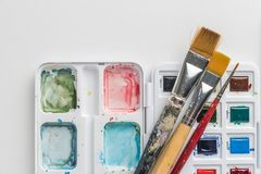 Box of watercolor paints and brushes royalty free stock photography