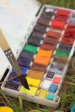 Box of watercolors with a brush on the grass. Outdoor painting with paints and brush royalty free stock photos
