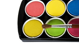 Box of watercolors and paintbrush. Black box of watercolors isolated on a white background royalty free stock photo