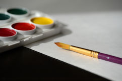Box with watercolors, white paper and a paintbrush Royalty Free Stock Photos