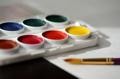 Box with watercolors, white paper and a paintbrush Royalty Free Stock Photo