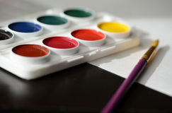 Box with watercolors, white paper and a paintbrush Royalty Free Stock Photography