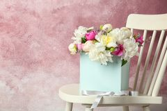 Free Box With Beautiful Flowers On Wooden Chair Against Color Background Royalty Free Stock Image - 118218896