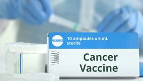 Box With Cancer Vaccine On The Table Against Blurred Lab Assistant. Fictional Phaceutical Logo Royalty Free Stock Photo