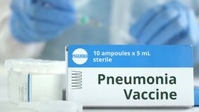 Box With Pneumonia Vaccine On The Table Against Blurred Lab Assistant. Fictional Phaceutical Logo Stock Image