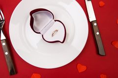 Box witha ring, table setting on a red background. Concept Valentine`s Day. - Image stock photos