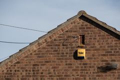Newly installed alarm system and box seen attached to the outside wall of a home. stock images