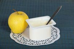 Box with yogurt, apple and a napkin. On blue background Royalty Free Stock Image