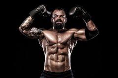 Boxare med tatueringen i boxninghandskar som firar prickfri seger Sportbegrepp som isoleras på svart bakgrund arkivbild
